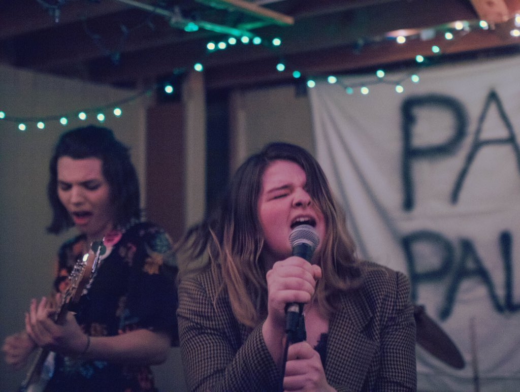Adeline performs on-stage at the DIY venue Panda Palace! Another bandmate is pictured in the background, as well as fairy lights, a banner with the name 'Panda Palace' spray-painted on it, and Adeline singing energetically into a microphone.