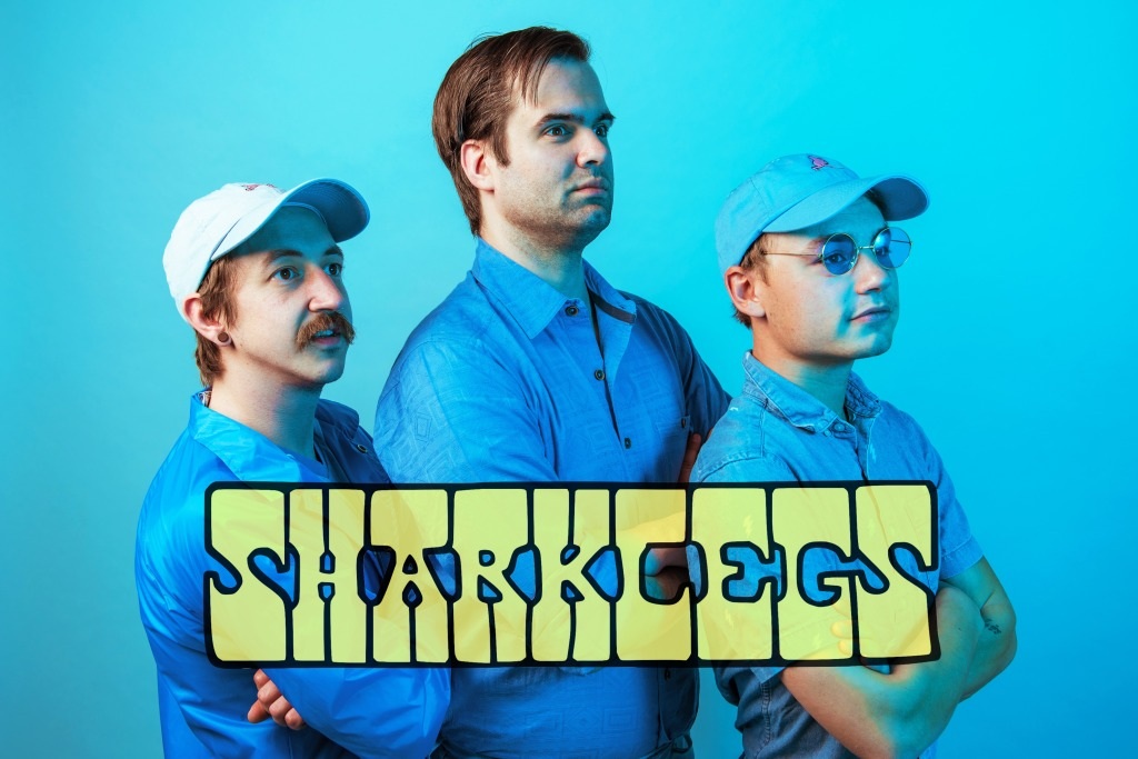 A vibrantly blue-toned image of the three musicians in the band SHARKLEGS, crossing their arms and looking dramatically off into the distance. 'SHARKLEGS' is written in a yellow 70's groovy font style across the image.